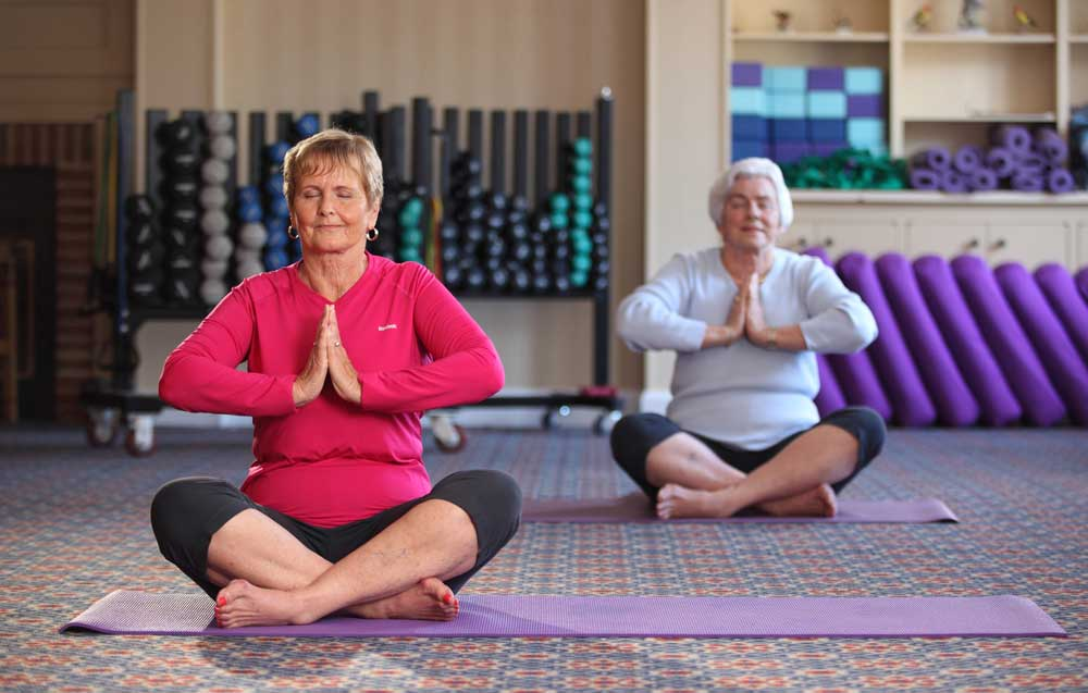 Two ladies practice yoga in our fitness center