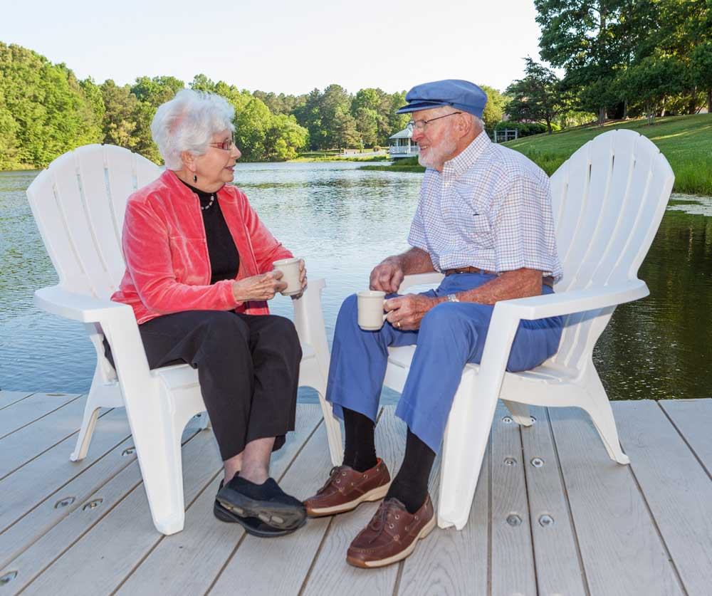 A woman and a man enjoy a pleasant conversation on the dock at the lake
