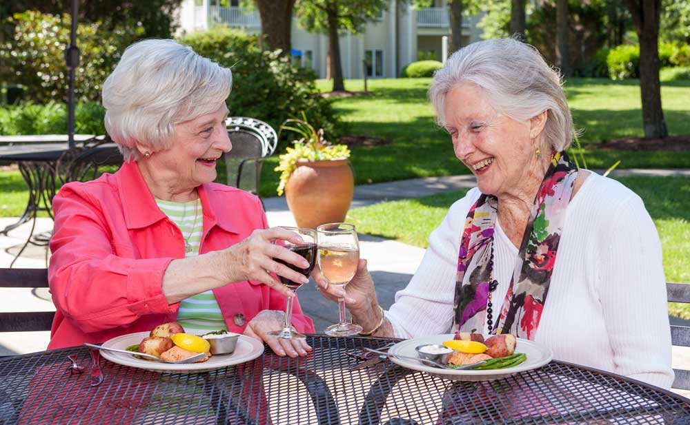 Two women enjoy fine dining on the outdoor patio at the Lakeside Grille