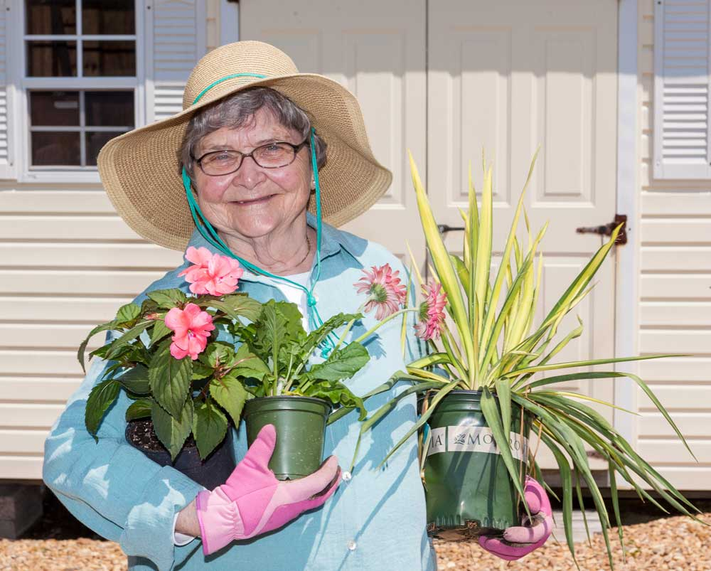 A woman enjoys planting new flowers in her garden